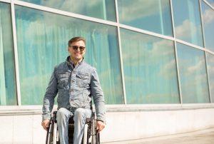 man in rolstoel voor woning
