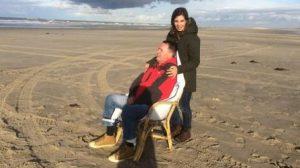 vrouw en man in stoel op strand