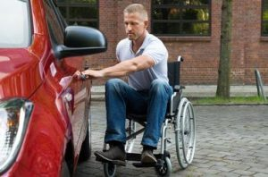 man in rolstoel naast auto