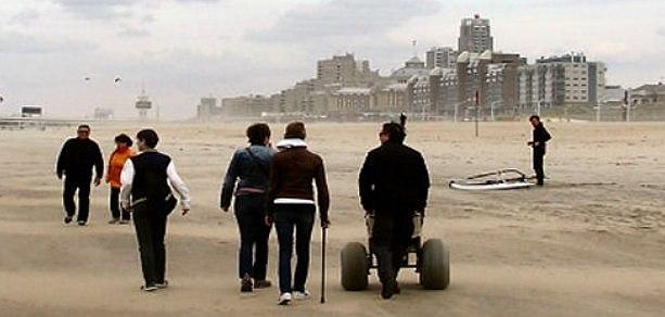 wandelaars met speciale rolstoel op het strand