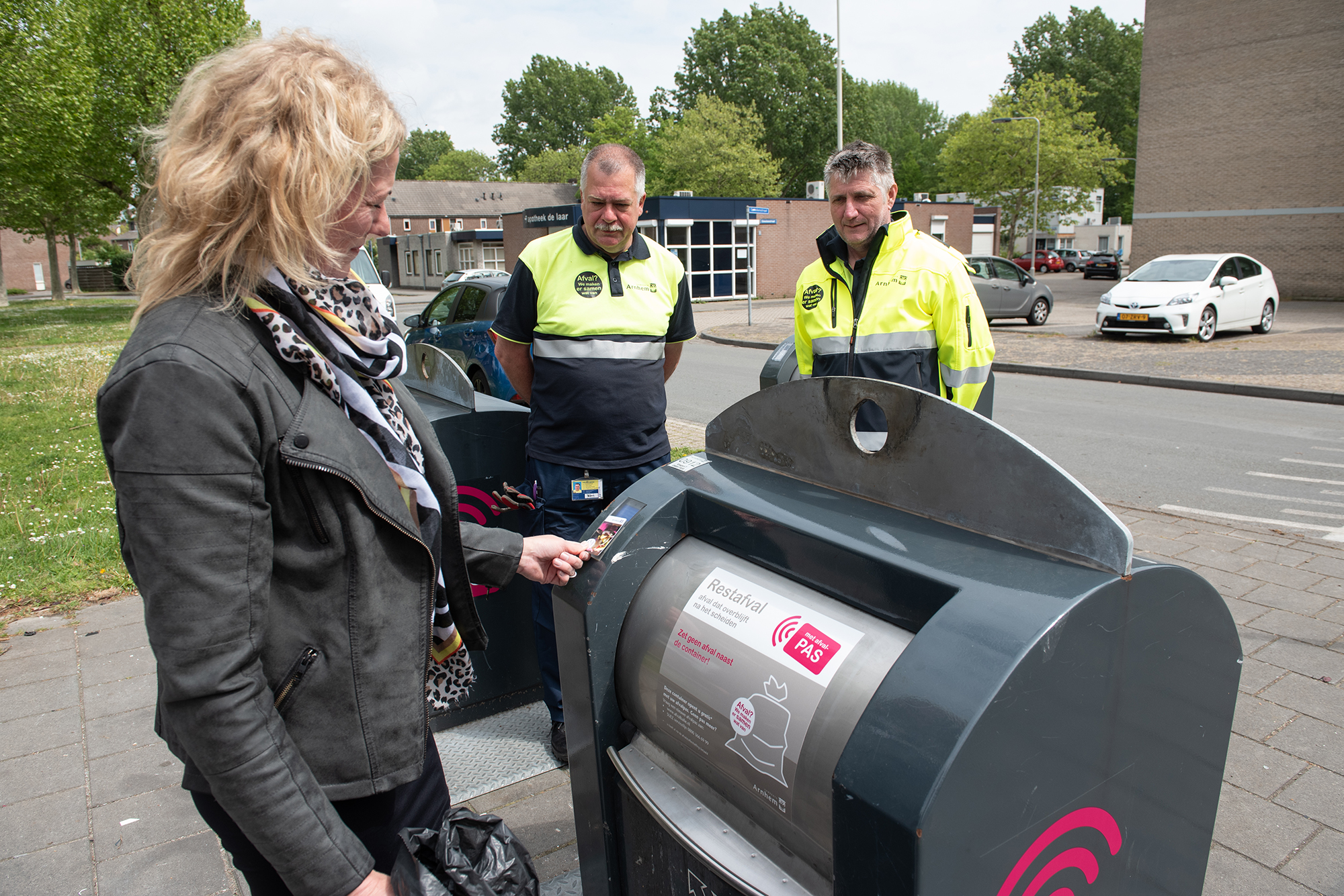 vrouw houdt pasje voor afvalcontainer