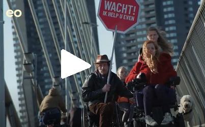 Mari en anderen met bord waarop staat: wacht, ik help u even